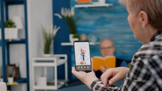Vrouw van middelbare leeftijd die praat tijdens videoconferentiegesprekken met externe arts die smartphone gebruikt