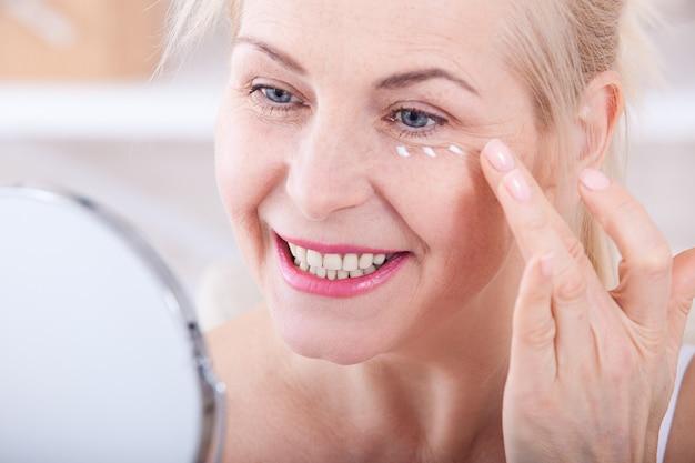Vrouw van middelbare leeftijd die rimpels in spiegel bekijkt. selectieve aandacht
