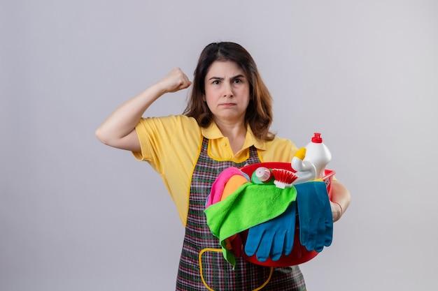 Vrouw van middelbare leeftijd die schort draagt ?? die emmer met schoonmakende hulpmiddelen houdt die ontevreden met fronsend gezicht kijkt dat vuist opheft die zich over witte muur bevindt