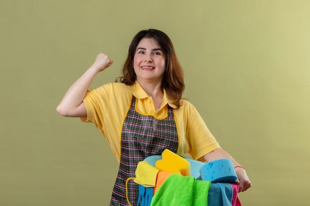 Vrouw van middelbare leeftijd die schort draagt ?? die emmer met schoonmakende hulpmiddelen houdt die vuist opheft die zich verheugt over haar succes glimlachend vrolijk kijkt zelfverzekerd staand over groene muur