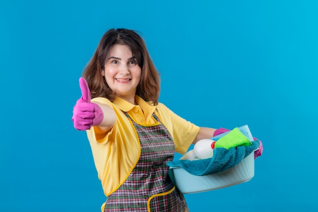Vrouw van middelbare leeftijd die schort en rubberhandschoenen draagt die bassin met schoonmakende hulpmiddelen houden