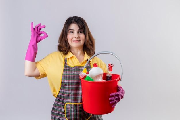 Vrouw van middelbare leeftijd die schort en rubberhandschoenen draagt die emmer met schoonmakende hulpmiddelen houden