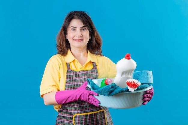 Vrouw van middelbare leeftijd die schort en rubberhandschoenenbassin met schoonmakende hulpmiddelen draagt