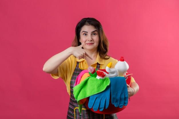 Vrouw van middelbare leeftijd die schort met emmer met schoonmaakgereedschap draagt en met de vinger ernaar wijst glimlachend staande over roze muur 3