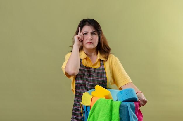 Vrouw van middelbare leeftijd die schort met emmer met schoonmaakgereedschap draagt, wijzende vinger omhoog en herinnert zichzelf eraan om het belangrijkste niet te vergeten