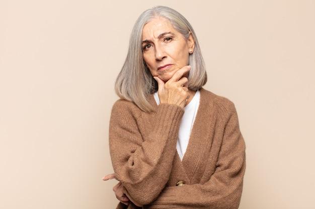 Vrouw van middelbare leeftijd die serieus, attent en wantrouwend kijkt, met één arm gekruist en hand op de kin, opties voor het wegen