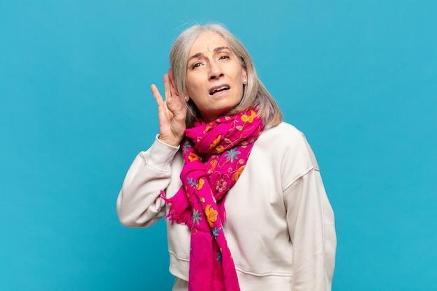 Vrouw van middelbare leeftijd die serieus en nieuwsgierig kijkt, luistert, een geheim gesprek of roddel probeert te horen, afluistert