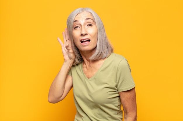 Vrouw van middelbare leeftijd die serieus en nieuwsgierig kijkt, luistert, probeert een geheim gesprek of roddel te horen, afluistert