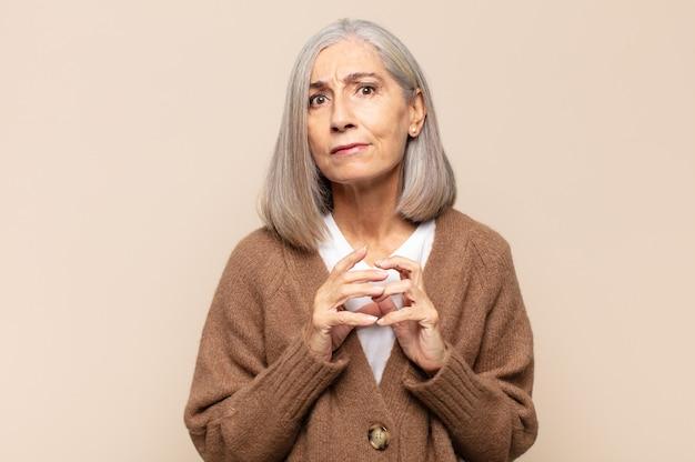 Vrouw van middelbare leeftijd die sluwheid en samenzwering bedenkt, sluwe trucs en bedriegers bedenkt, sluwheid en verraad