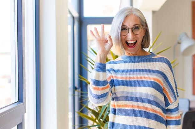 Vrouw van middelbare leeftijd die succesvol en tevreden voelt, glimlachend met wijd open mond, goed teken met hand maakt
