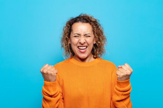 Vrouw van middelbare leeftijd die triomfantelijk schreeuwt, lacht en zich blij en opgewonden voelt terwijl ze succes viert