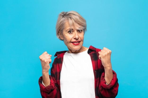 Vrouw van middelbare leeftijd die triomfantelijk schreeuwt, lacht en zich gelukkig en opgewonden voelt terwijl ze succes viert