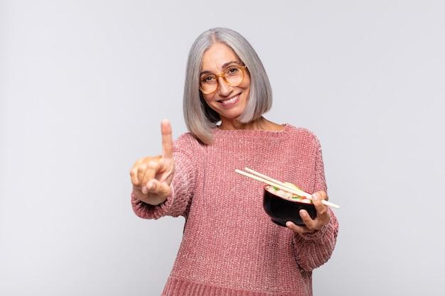 Vrouw van middelbare leeftijd die trots en zelfverzekerd glimlacht en nummer één triomfantelijk laat poseren, zich als een leider aziatisch voedselconcept