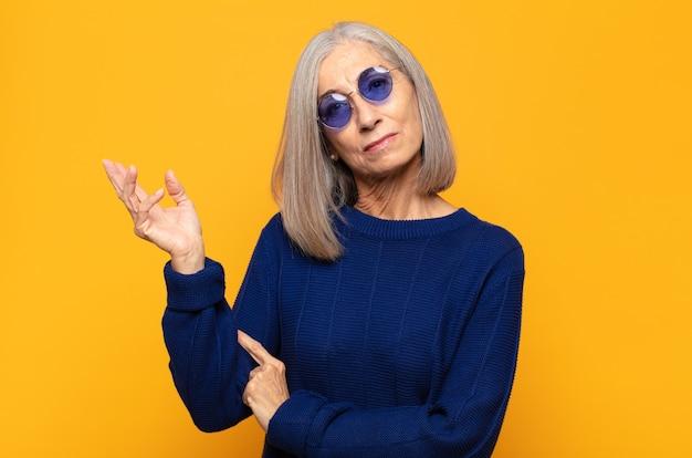 Vrouw van middelbare leeftijd die trots en zelfverzekerd glimlacht, zich gelukkig en tevreden voelt en een concept toont op kopie ruimte