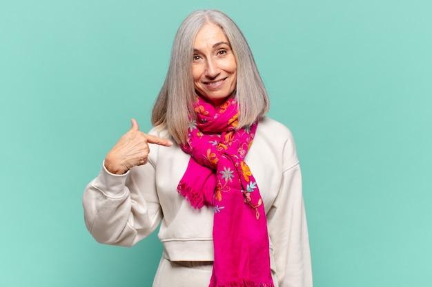 Vrouw van middelbare leeftijd die trots, zelfverzekerd en gelukkig kijkt, glimlacht en naar zichzelf wijst of nummer één maakt