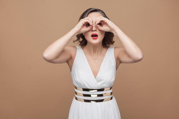 Vrouw van middelbare leeftijd die ver weg kijkt op een verrekijkergebaar emotioneel uitdrukkende vrouw in witte jurk, rode lippen en donker krullend kapsel. studio-opname, binnen, geïsoleerd op beige of lichtbruine achtergrond
