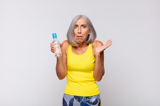 Vrouw van middelbare leeftijd die verbaasd en geschokt kijkt, met open mond een voorwerp in haar handen