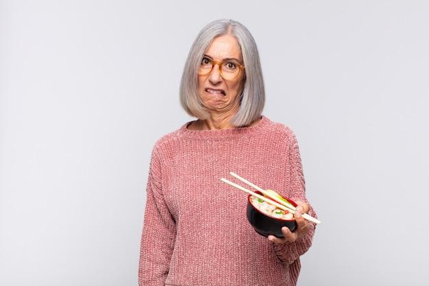 Vrouw van middelbare leeftijd die verbaasd en verward kijkt, lip bijt met een nerveus gebaar, het antwoord op het probleem aziatische voedselconcept niet weet