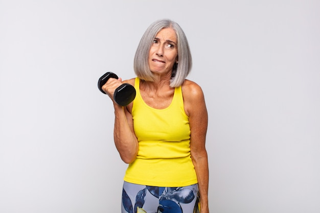 Vrouw van middelbare leeftijd die verbaasd en verward kijkt, op lip bijt met een nerveus gebaar, het antwoord op het probleem niet weet. fitness concept