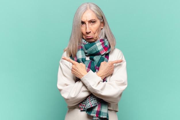 Vrouw van middelbare leeftijd die verbaasd en verward, onzeker en in tegengestelde richting wijst met twijfels