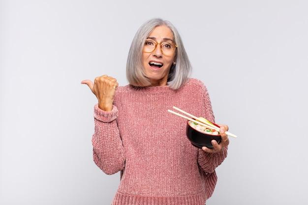 Vrouw van middelbare leeftijd die verbaasd van ongeloof kijkt, naar een voorwerp aan de zijkant wijst en wauw zegt, ongelooflijk aziatisch voedselconcept