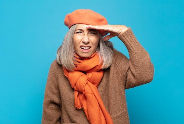 Vrouw van middelbare leeftijd die verbijsterd en verbaasd kijkt, met hand over voorhoofd ver weg kijkend, kijkend of zoekend