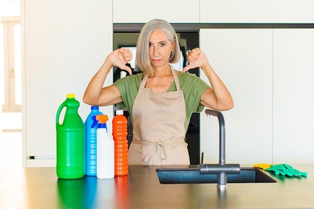 Vrouw van middelbare leeftijd die verdrietig, teleurgesteld of boos kijkt, duimen naar beneden laat zien bij onenigheid, zich gefrustreerd voelt