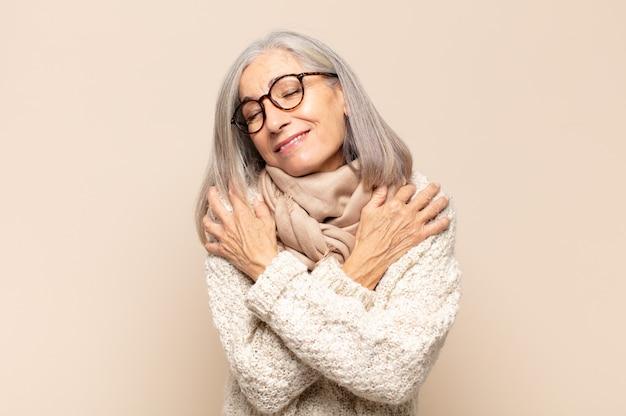 Vrouw van middelbare leeftijd die verliefd is, glimlacht, zichzelf knuffelt en knuffelt, vrijgezel blijft, egoïstisch en egocentrisch is