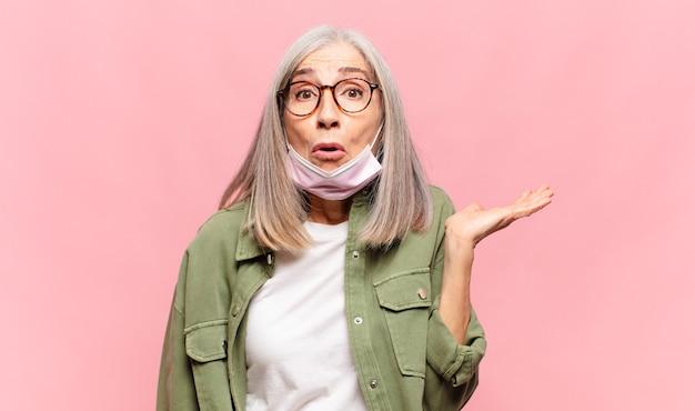 Vrouw van middelbare leeftijd die verrast en geschokt kijkt, met open mond en een object vasthoudt met een open hand aan de zijkant