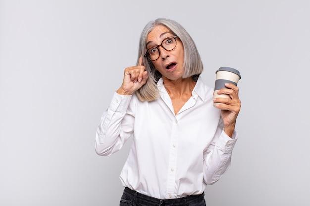 Vrouw van middelbare leeftijd die verrast, met open mond en geschokt kijkt