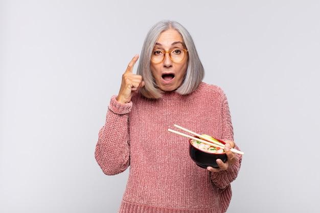 Vrouw van middelbare leeftijd die verrast, met open mond, geschokt kijkt, een nieuwe gedachte, idee of concept aziatisch voedselconcept realiseert
