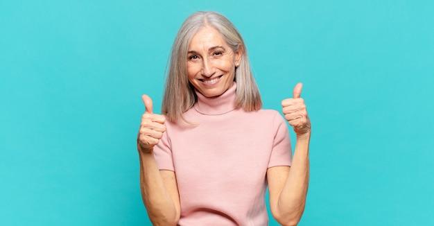 Vrouw van middelbare leeftijd die vreugdevol glimlacht en er gelukkig uitziet, zich zorgeloos en positief voelt met beide duimen omhoog