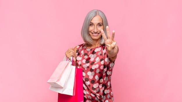 Vrouw van middelbare leeftijd die vriendelijk glimlacht en kijkt, nummer drie toont
