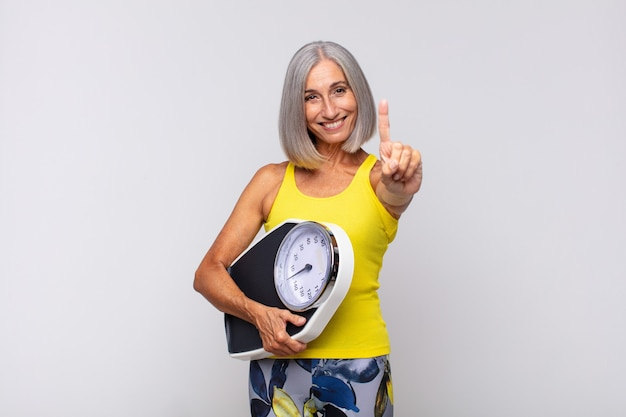 Vrouw van middelbare leeftijd die vriendelijk glimlacht en kijkt, nummer één toont