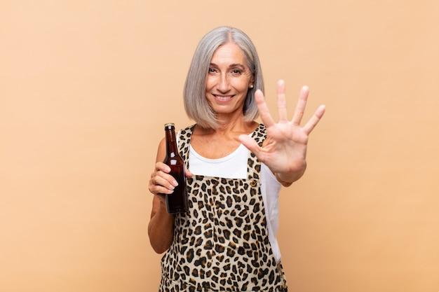 Vrouw van middelbare leeftijd die vriendelijk glimlacht en kijkt, nummer vijf of vijfde met vooruit hand toont, aftellend met een biertje