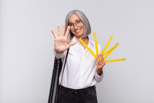Vrouw van middelbare leeftijd die vriendelijk glimlacht kijkt, nummer vijf of vijfde met vooruit hand toont, aftellend
