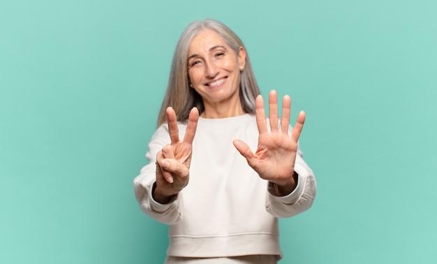 Vrouw van middelbare leeftijd die vriendelijk glimlacht kijkt, nummer zeven of zevende met vooruit hand toont, aftellend