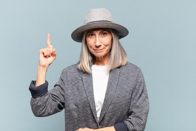 Vrouw van middelbare leeftijd die vrolijk en gelukkig glimlacht, naar boven wijzend met één hand om ruimte te kopiëren