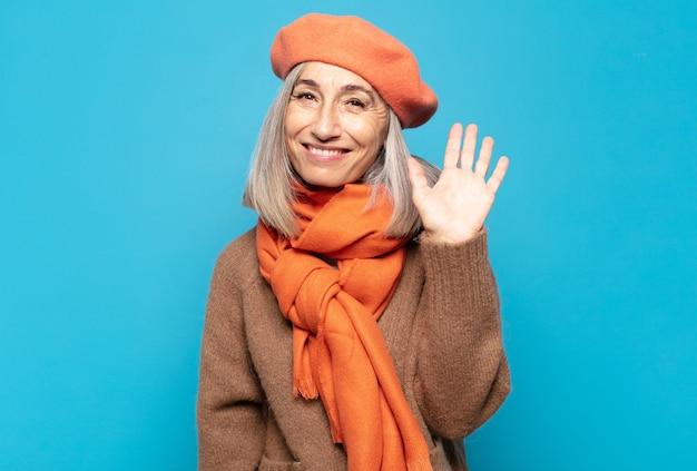 Vrouw van middelbare leeftijd die vrolijk en opgewekt glimlacht, hand zwaait, u verwelkomt en begroet, of afscheid neemt