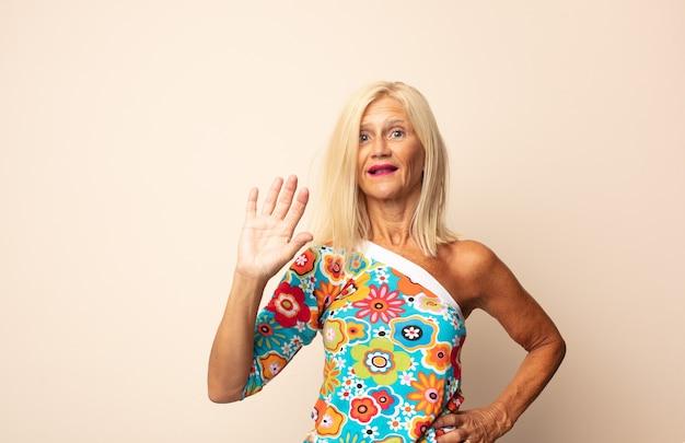 Vrouw van middelbare leeftijd die vrolijk en opgewekt lacht, met de hand zwaait, je verwelkomt en begroet, of afscheid neemt