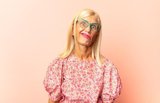 Vrouw van middelbare leeftijd die vrolijk en terloops glimlacht, naar beneden kijkt en naar de borst wijst