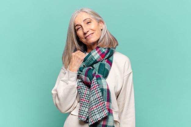 Vrouw van middelbare leeftijd die vrolijk en zelfverzekerd lacht met een ongedwongen, vrolijke, vriendelijke glimlach