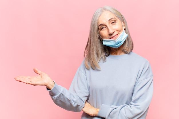 Vrouw van middelbare leeftijd die vrolijk glimlacht, zich gelukkig voelt en een concept in exemplaarruimte met handpalm toont