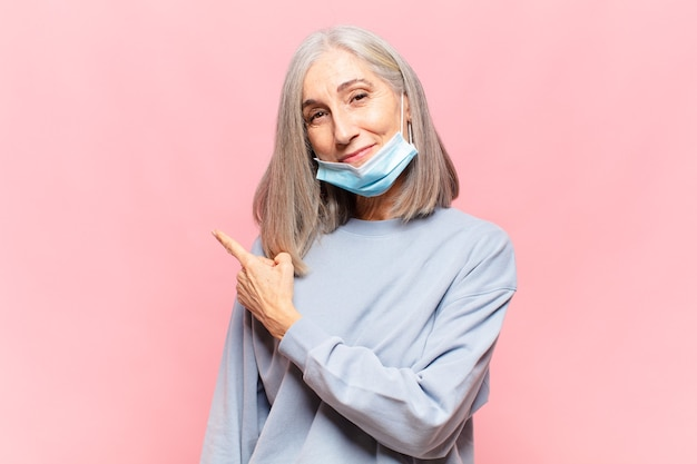 Vrouw van middelbare leeftijd die vrolijk glimlacht, zich gelukkig voelt en naar de zijkant en naar boven wijst, object in kopie ruimte toont