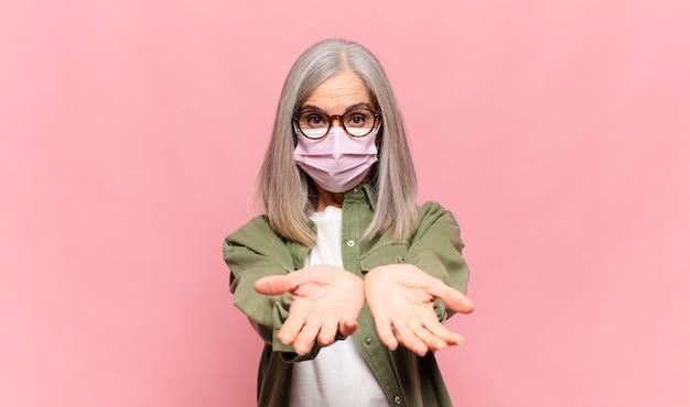 Vrouw van middelbare leeftijd die vrolijk lacht met een vriendelijke, zelfverzekerde, positieve blik, een object of concept aanbiedt en toont