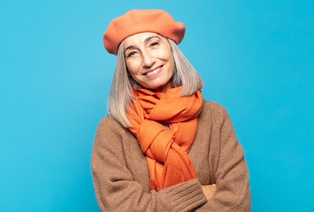 Vrouw van middelbare leeftijd die vrolijk lacht met gekruiste armen, met een ontspannen, positieve en tevreden pose