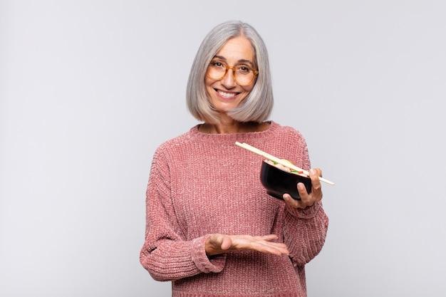 Vrouw van middelbare leeftijd die vrolijk lacht, zich gelukkig voelt en een concept in kopieerruimte laat zien met een handpalm aziatisch voedselconcept