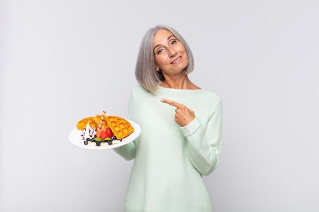 Vrouw van middelbare leeftijd die vrolijk lacht, zich gelukkig voelt en naar de zijkant en naar boven wijst, een object in de kopieerruimte laat zien. ontbijt concept