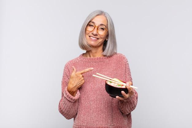 Vrouw van middelbare leeftijd die vrolijk lacht, zich gelukkig voelt en naar de zijkant en naar boven wijst, object toont in kopie ruimte aziatisch eten concept