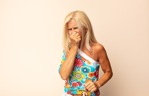 Vrouw van middelbare leeftijd die walging voelt, neus vasthoudt om te voorkomen dat ze een vieze en onaangename stank ruikt